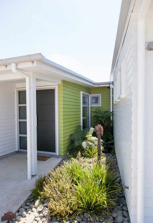 painted weatherboards, white house, green feature wall, green entranceway, house exterior