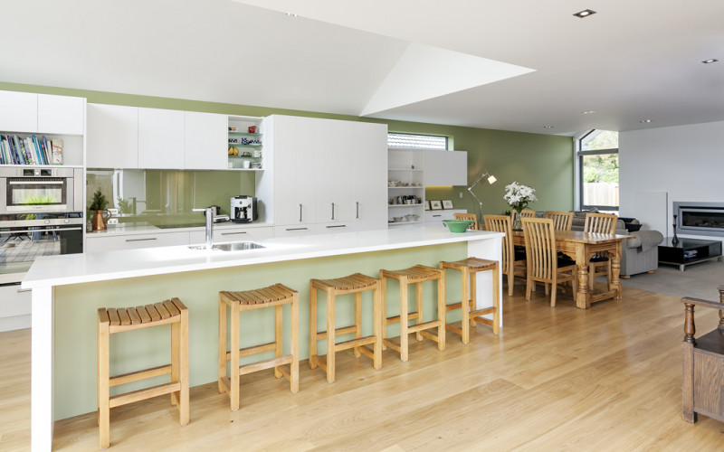 green kitchen, living area, wooden floors, green splashback, lounge, green and white paint