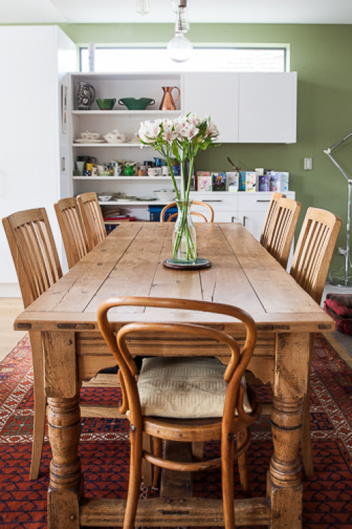 dining room, wooden dining table and chairs, green feature wall, green kitchen